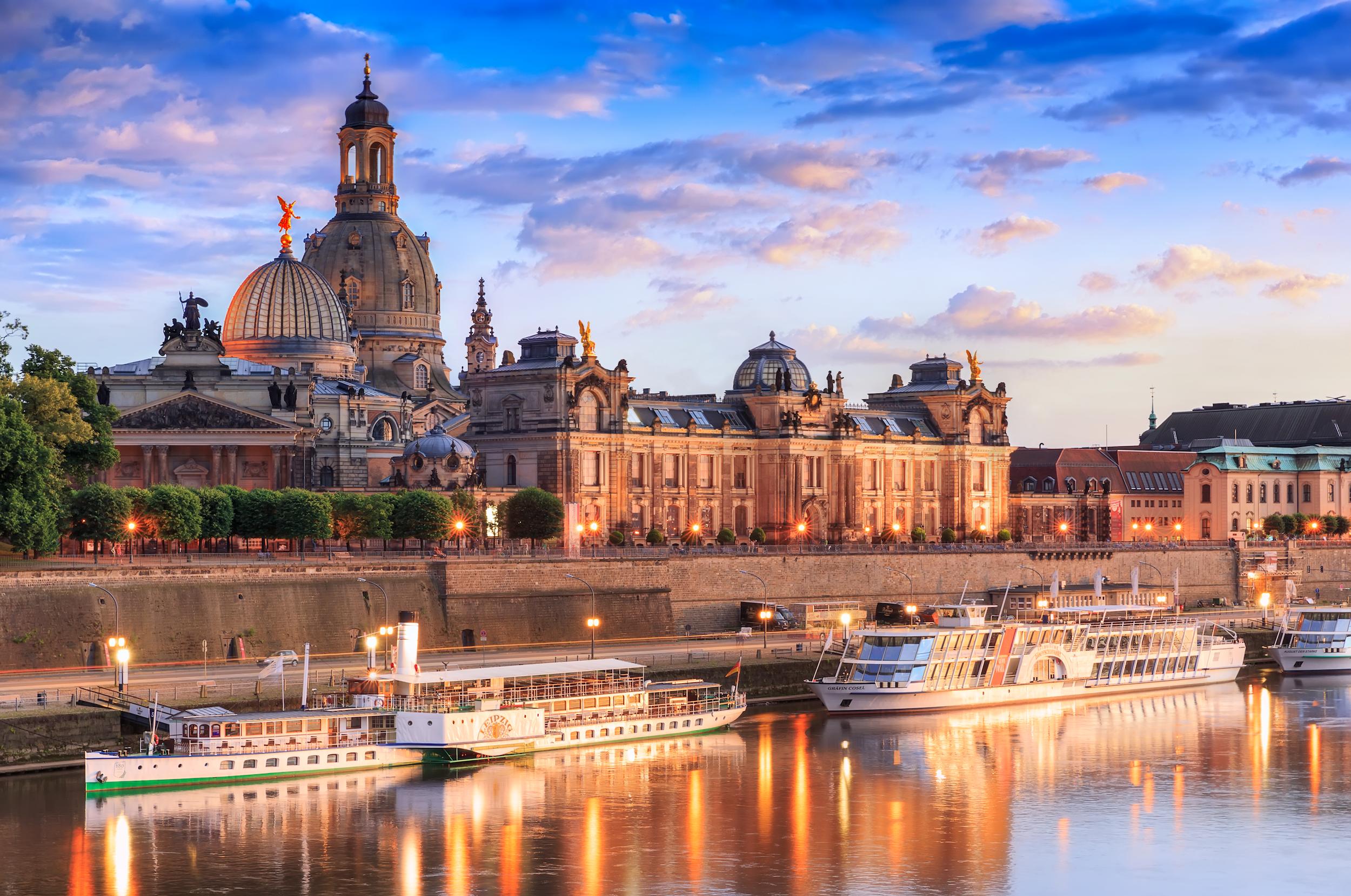 Elbterassen vor der Altstad Dresdens mit Blick auf die Kunstakademi, die Frauenkirche und weitere Gebäude. In der Elbe liegen drei Schiffe der Elbflotte am Kai. Es ist abendliche Stimmung und die ersten Beleuchtungen sind angeschaltet worden.